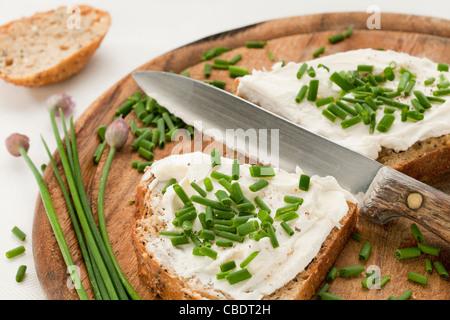 Vollkorn-Brotscheiben mit Frischkäse, grüne gehackter Schnittlauch. Spanner und Salz auf ein Holz Schneidebrett - Stockfoto
