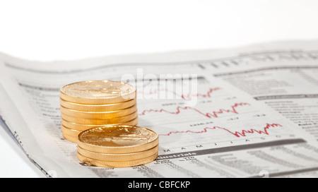 Gold Eagle 1 Unze Münzen gestapelt in Spalten im Wirtschaftsteil der Zeitung mit Diagrammen - Stockfoto