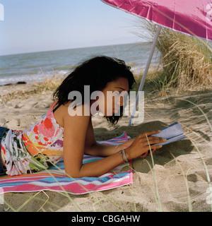 Ein junges Mädchen am Strand ein Buch lesen - Stockfoto