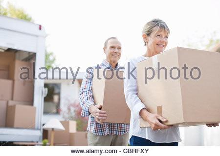 Paar entladen Kisten von Umzugswagen - Stockfoto