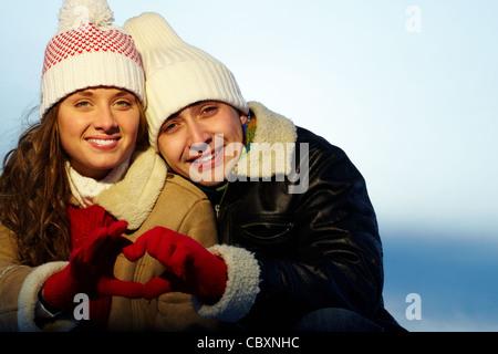 Porträt des glücklichen Paares in Winterkleidung machen Herzen durch die Hände - Stockfoto