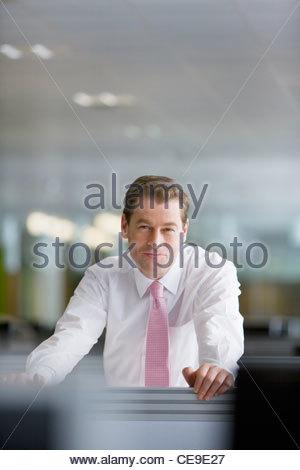 Porträt von lächelnden Geschäftsmann stützte sich auf den Schreibtisch im Büro - Stockfoto