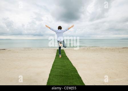 Mann steht auf einem Bein am Ende des Teppichs mit Arme ausgestreckt, hintere Ansicht am Strand - Stockfoto