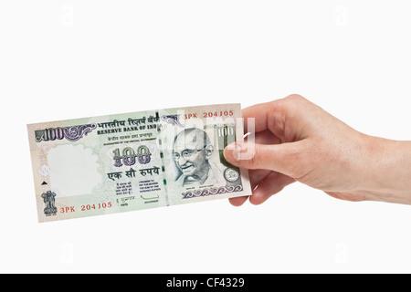Eine indische 100 Rupien Rechnung mit dem Porträt von Mahatma Gandhi ist in der Hand, weißen Hintergrund gehalten. - Stockfoto