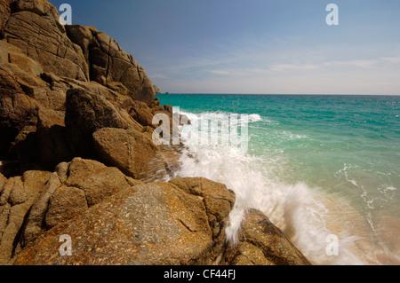 Wellen um Felsen am Cornish Strand von Porthcurno. - Stockfoto