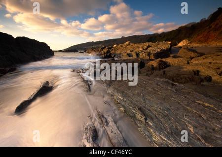 Wellen in und um Felsen auf das Vorland der Stoke-Strand in der Nähe von Plymouth. - Stockfoto