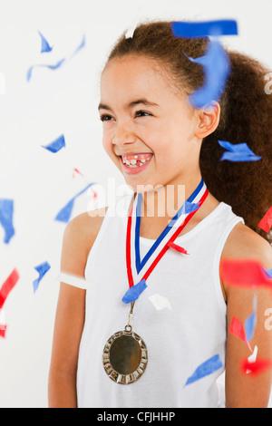 Mädchen tragen Medaille mit Ticker Tape fallen - Stockfoto