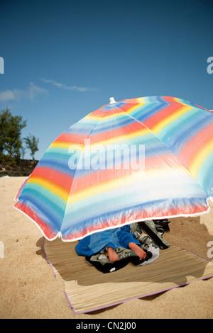 Junge liegend unter Sonnenschirm am Sandstrand - Stockfoto