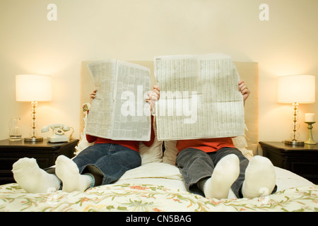 Paar lesen Zeitungen im Bett, Toronto, Ontario - Stockfoto