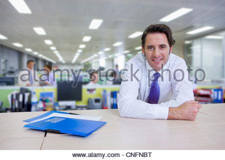 Porträt von zuversichtlich Geschäftsmann stützte sich auf Schrank im Büro - Stockfoto