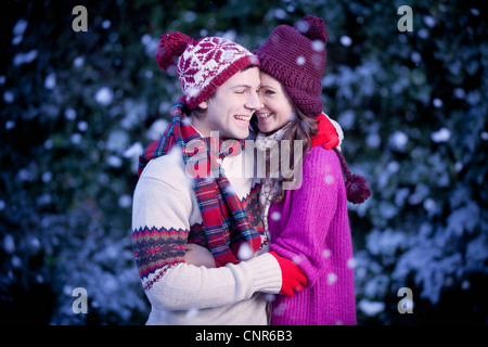 Lächelnde paar umarmt im Schnee - Stockfoto