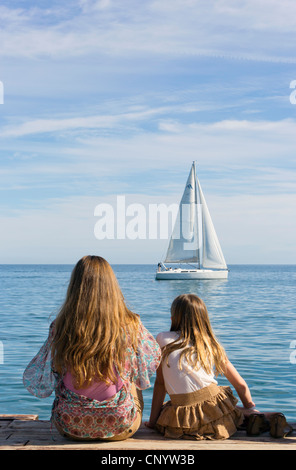 Junge Frau und kleine Mädchen saß am Ende des hölzernen Steg beobachten ein Segelboot vorbeiziehen. - Stockfoto