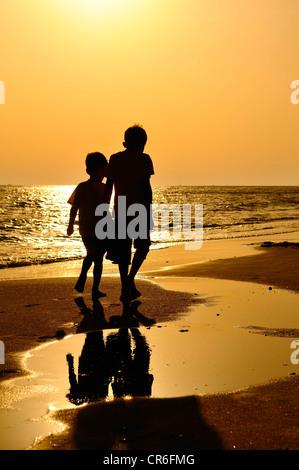 Zwei jungen, die zu Fuß am Strand, Abendstimmung, Lido di Ostia, Rom, Latium, Italien, Europa - Stockfoto