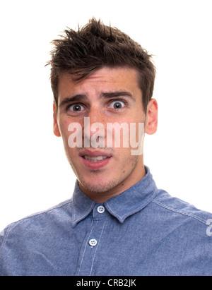Ein Mann zeigt ein *** Ausdruck in einem blauen Hemd auf einem weißen Hintergrund. - Stockfoto