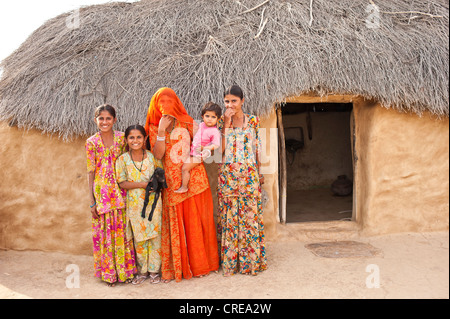 Neugierige Mädchen und jungen Frau vor ihrem Haus stand, eine verschleierte junge Frau trägt einen roten Sari trägt - Stockfoto
