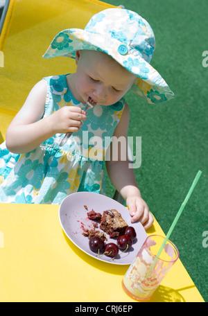 kleines Mädchen im Sommer Tuch mit Sonnenhut sitzen am Tisch für Kinder im Garten Kirsch Kuchen essen - Stockfoto