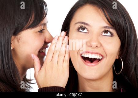 junge Frau ein Geheimnis erzählen, ihre Freundin - sie sucht amüsiert - Stockfoto