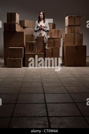Teenager-Mädchen in Haufen von Kartons - Stockfoto