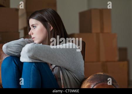 Teenager-Mädchen im Sessel im neuen Zuhause - Stockfoto