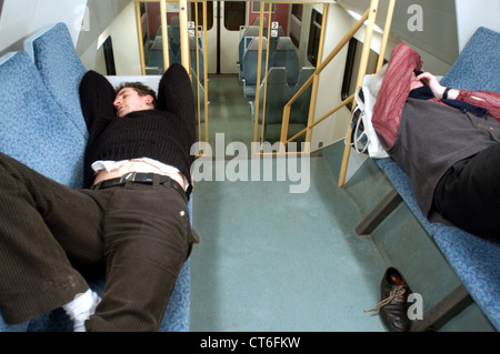 Männer schlafen in einem Regionalzug - Stockfoto