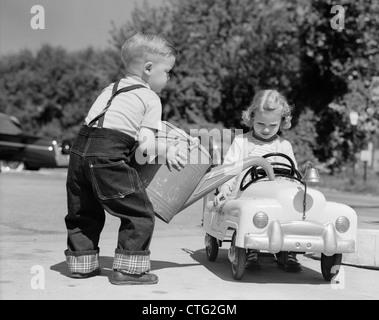 1950ER JAHREN KLEINER JUNGE SPIELT TANKSTELLE GIEßEN WASSER IN SPIELZEUGAUTO FÜR KLEINE MÄDCHEN - Stockfoto