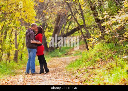 Jung verheiratet paar küssen bei einem Spaziergang In einem Park im Herbst; Edmonton, Alberta, Kanada - Stockfoto