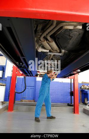 Garage Mechaniker unter Motor Car auf dem Hebezeug - Stockfoto