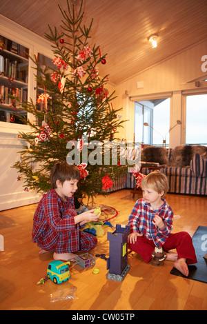 Jungs spielen unter Weihnachtsbaum - Stockfoto