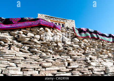 Zwei bunte gemusterte Teppiche hängen über einer handgefertigten Steinmauer mit einem Haus oben im Dorf Korzok, - Stockfoto