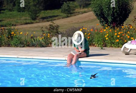 Junges Mädchen von etwa sitzt Alter von 12 Jahren Swimming Pool zu lesen, wie eine Schwalbe niedrig Vergangenheit - Stockfoto
