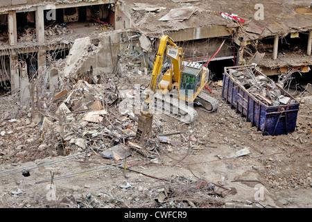 Hydraulikbagger verwendet wird, um aus den Trümmern eines abgerissenen Gebäudes für das recycling Schrott zu trennen - Stockfoto