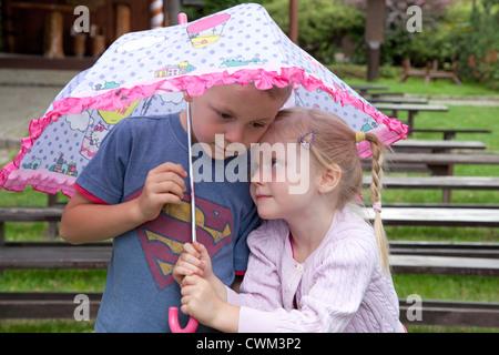 Liebevolle Kinder Geschwister jungen und Mädchen im Alter von 6 und 4 unter einem Sonnenschirm. Spala Zentralpolen - Stockfoto