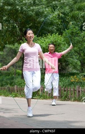 Älteres Paar spielen Seilspringen im park - Stockfoto