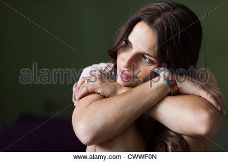 Lächelnde Frau umarmt die Knien - Stockfoto