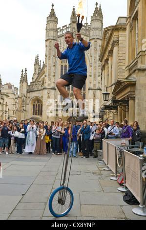 Straße Entertainer auf Einrad, Jonglage, außen Bath Abbey und die Trinkhalle in Bad Somerset England UK - Stockfoto
