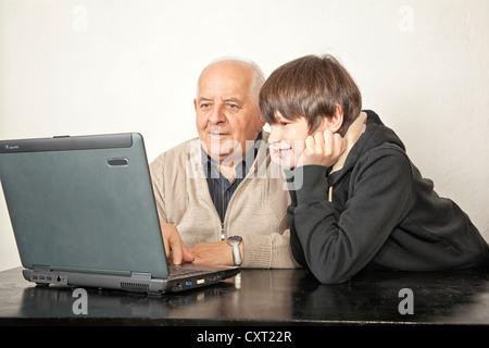 Ein Alter Mann und ein Junge sitzt vor einem laptop - Stockfoto