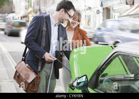 Paar Aufladen von Elektroautos auf die Straße - Stockfoto