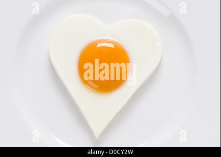 Gebratenes Ei oder Spiegelei in der Form eines Herzens auf eine weiße geformte Kreisplatte. Ei präsentiert weiche - Stockfoto