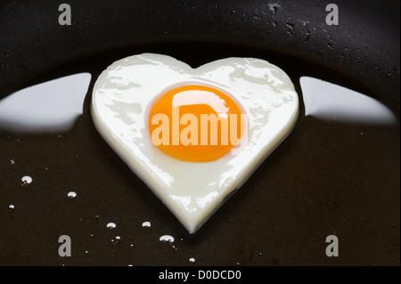 Spiegelei. herzförmige Hühner Ei Kochen in Öl in einer Pfanne in der Form eines Herzens zu Spiegelei - Stockfoto