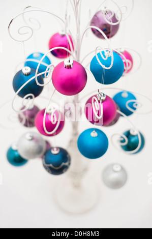 Bunte Weihnachtskugeln hängen von einem dekorativen Weißmetall-stand - Stockfoto