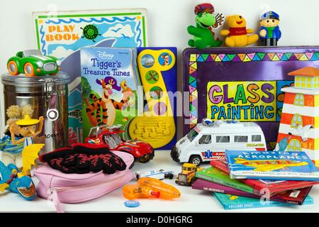 Sortierte Mischung von jungen und Mädchen Kinderspielzeug auf Regal einschließlich Miniautos, Teddybär, Handschuhe - Stockfoto