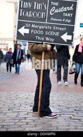 Ein Mann stand in der High Street hält ein Plakat mit Wegbeschreibungen für lokale Geschäfte. - Stockfoto