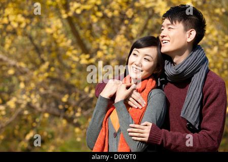 Glückliches junges Paar in Liebe Arm um Natur im Herbst - Stockfoto