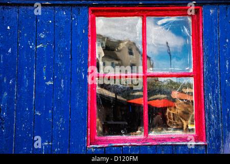 Reflexion In einem roten getrimmte Fenster auf ein blaues Gebäude; St. Abbs Head schottischen grenzt an Schottland - Stockfoto