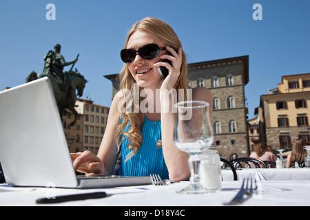 Junge Frau im Restaurant im Freien, mit Laptop und Handy - Stockfoto