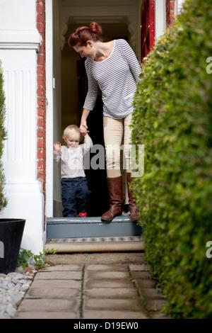 Mutter hilft kleinen Sohn über Haustür - Stockfoto