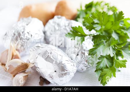 Rohe Kartoffeln eingewickelt in Alufolie, Essen Nahaufnahme - Stockfoto