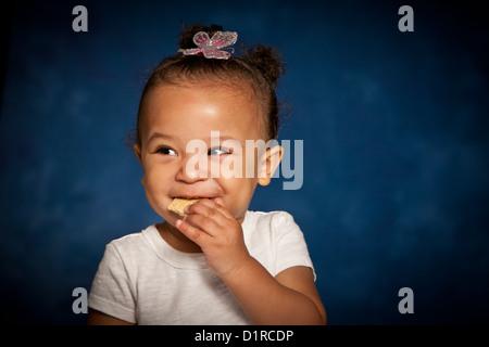 Nettes Studioportrait eine Mischrasse Kleinkind Mädchen essen einen Keks mit einem frechen Lächeln auf ihrem Gesicht - Stockfoto