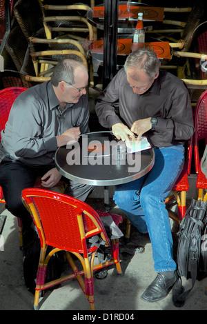 Zwei Männer sitzen an einem Paris-Café-Tisch eine Karte studieren und arbeiten, Richtung - Stockfoto