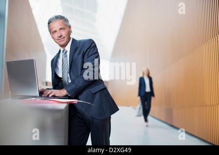 Porträt von zuversichtlich Geschäftsmann mit Laptop im Büro - Stockfoto
